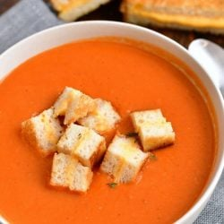 overhead photo: bowl of tomato soup with grilled cheese croutons - grilled cheese sandwich in background