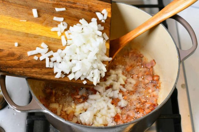 diced onion on wood cutting board being transferred to cooking pot