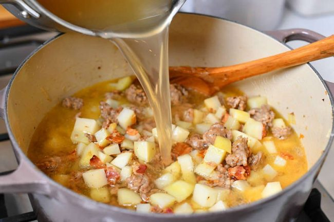 pouring chicken stock into soup pot with diced potatoes and Italian sausage