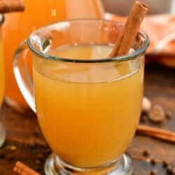 hot apple cider in glass mug garnished with cinnamon stick