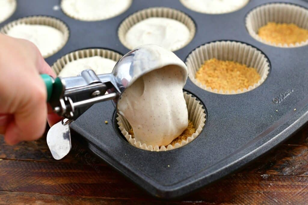scooping cheesecake batter into cupcake liner in baking pan