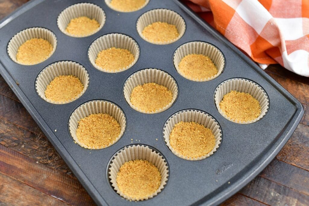 graham cracker crumb crusts in paper lined muffin pan