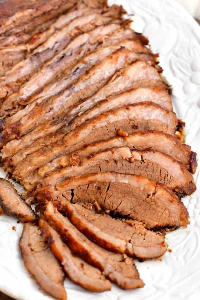 thin slices of oven baked beef brisket on white serving platter
