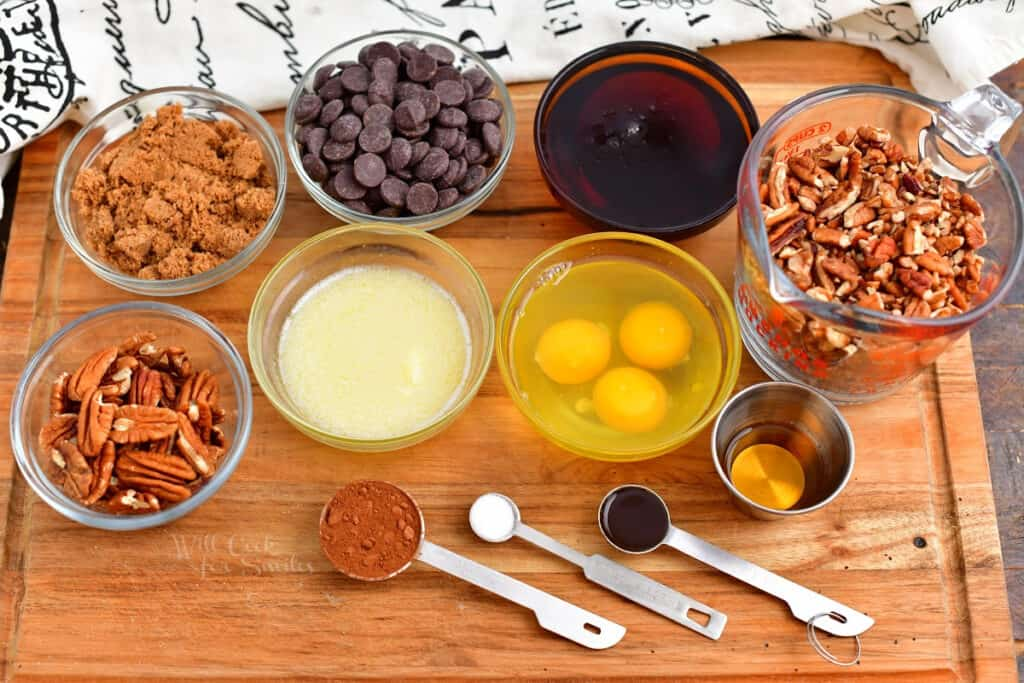 chocolate pecan pie recipe ingredients in prep bowls on wood cutting board