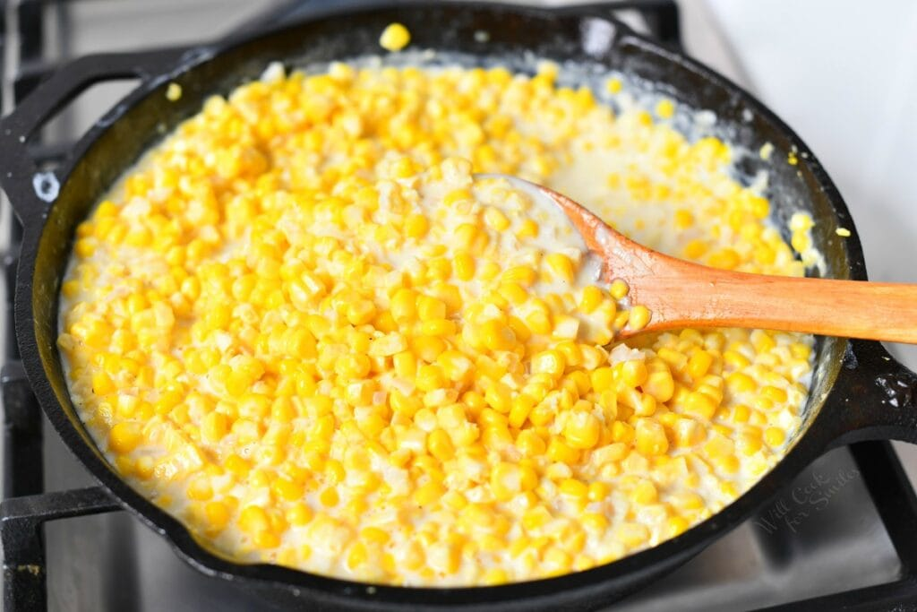 wooden spoon stirring creamed corn in cast iron skillet