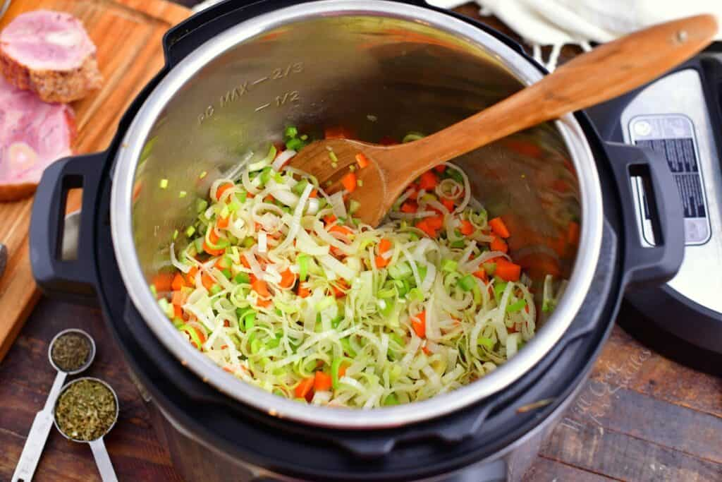 overhead image: stirring uncooked leeks and carrots in a pressure cooker