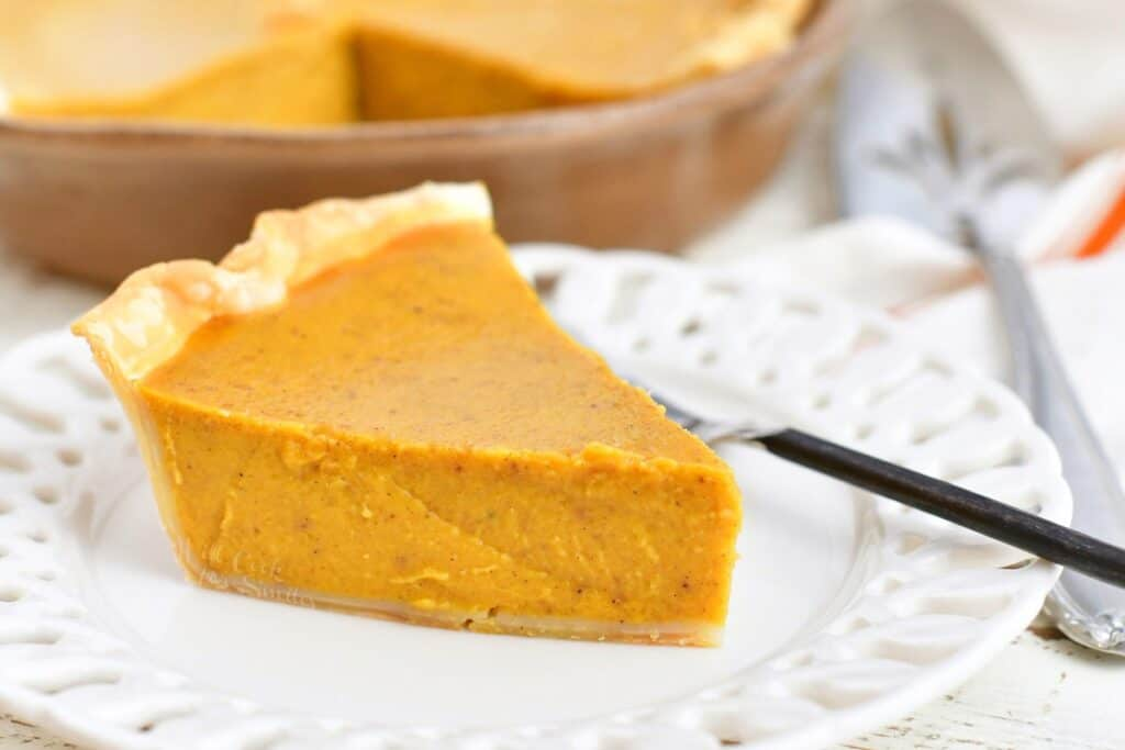 slice of pumpkin pie on a white plate with a fork