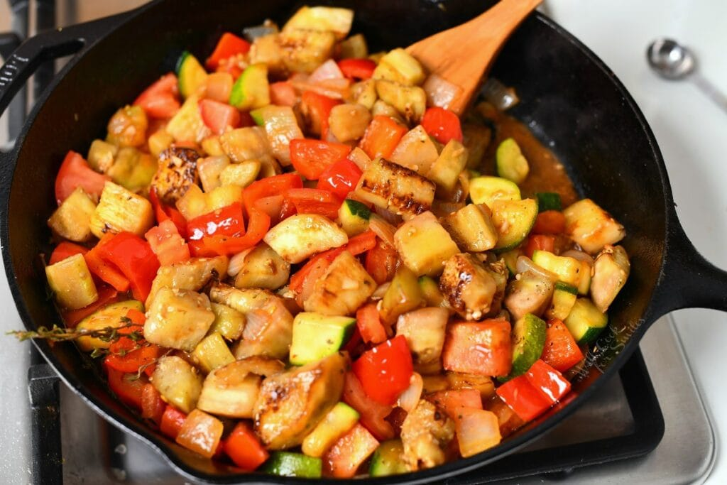 close up image of diced onions, red bell pepper, eggplant and zucchini cooking in cast iron skillet