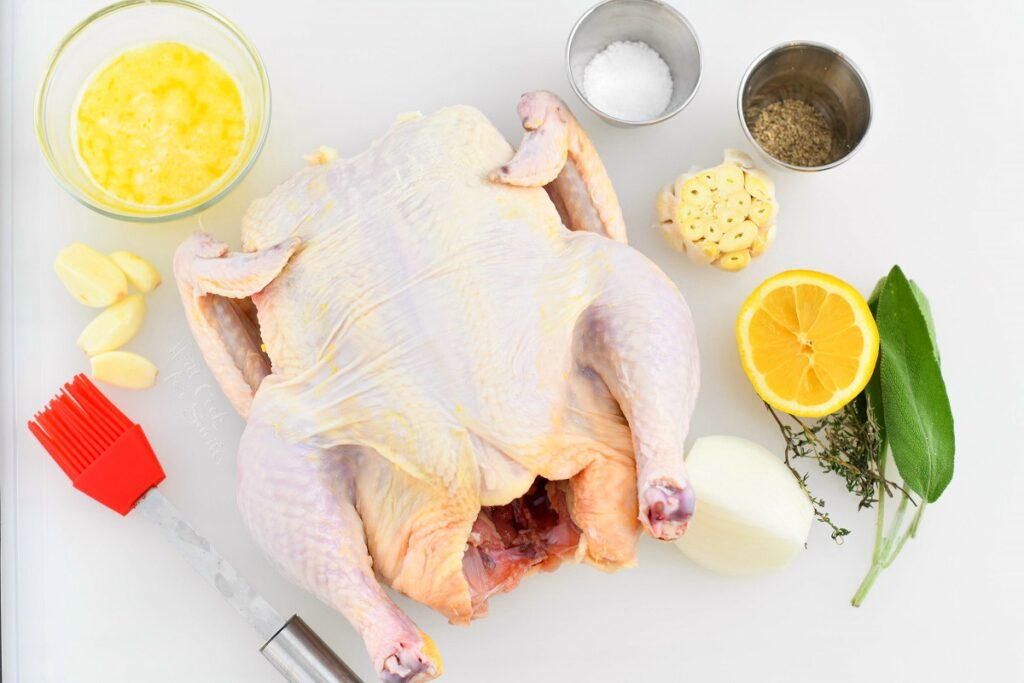 overhead photo: whole raw chicken, spices and herbs to make a roast chicken recipe