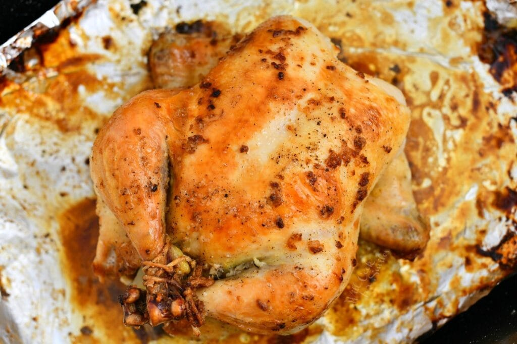 making a roast chicken recipe: trussed bird on sheet of aluminum foil in oven