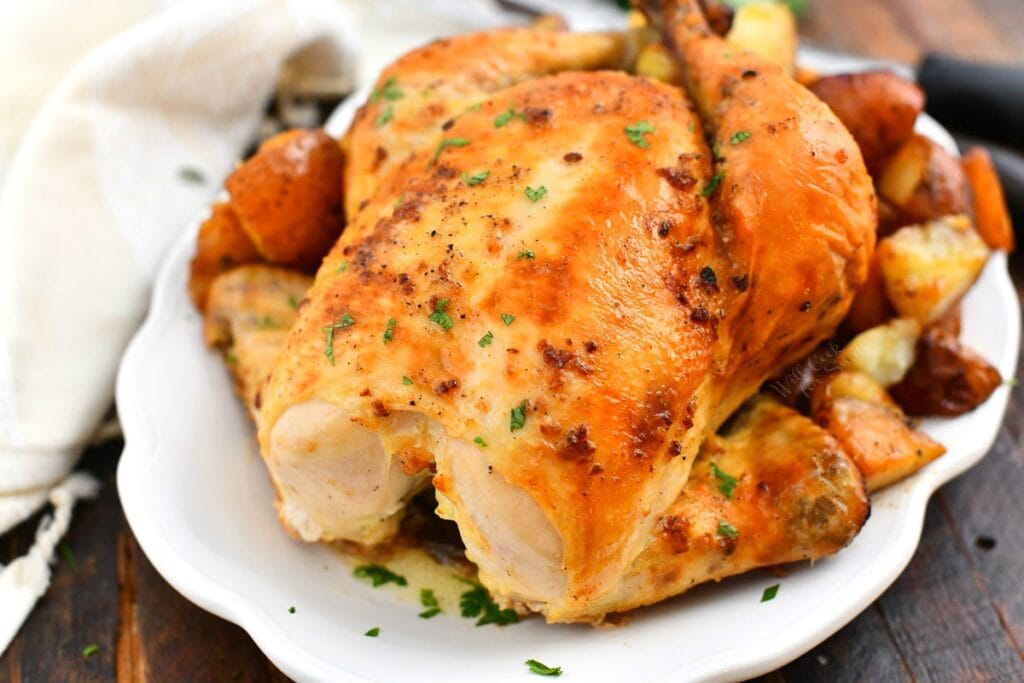 white serving platter of whole roasted chicken with crispy, golden skin