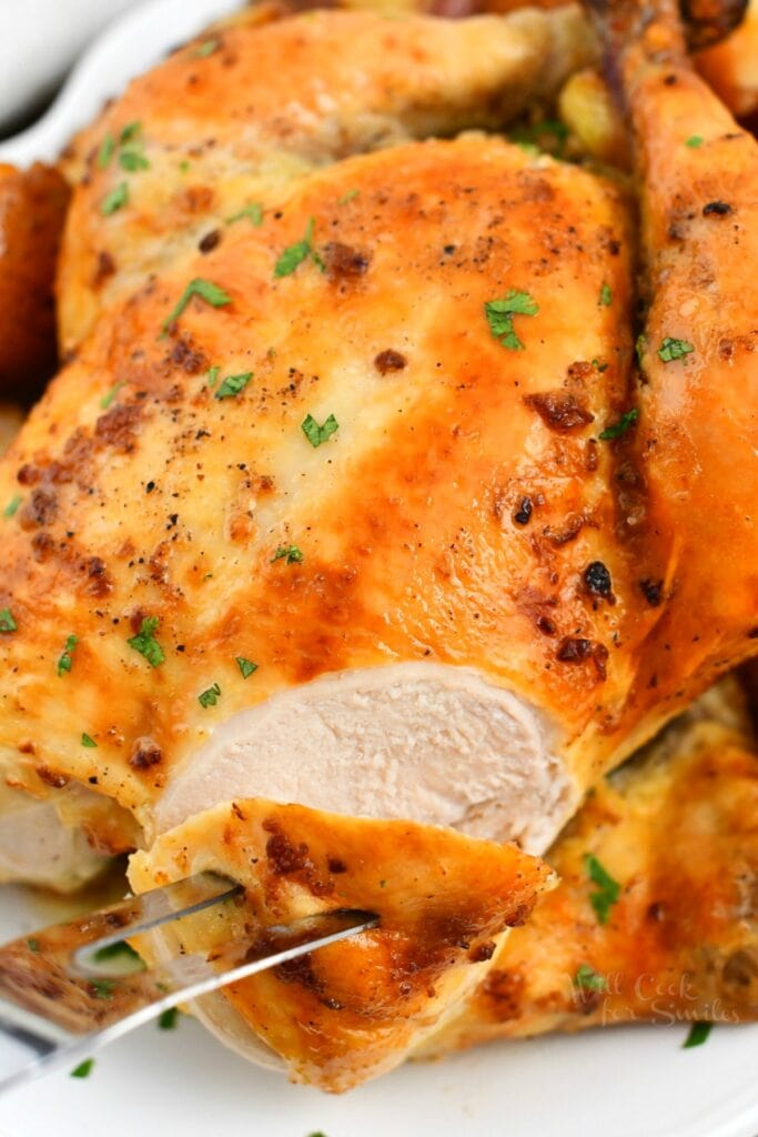 close up photo: carving crispy skinned whole chicken