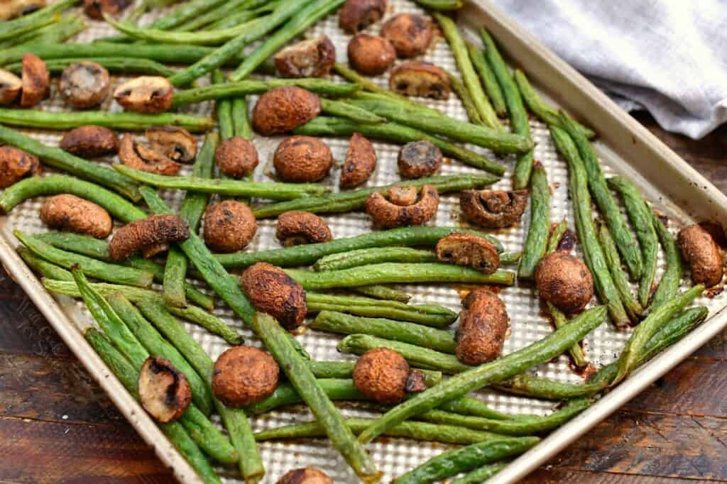 roasted green beans and mushrooms on rimmed baking sheet