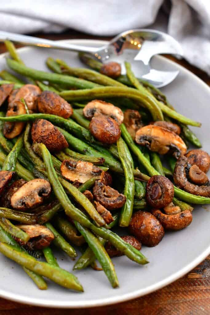 green bean and mushroom side dish in white bowl with serving spoon