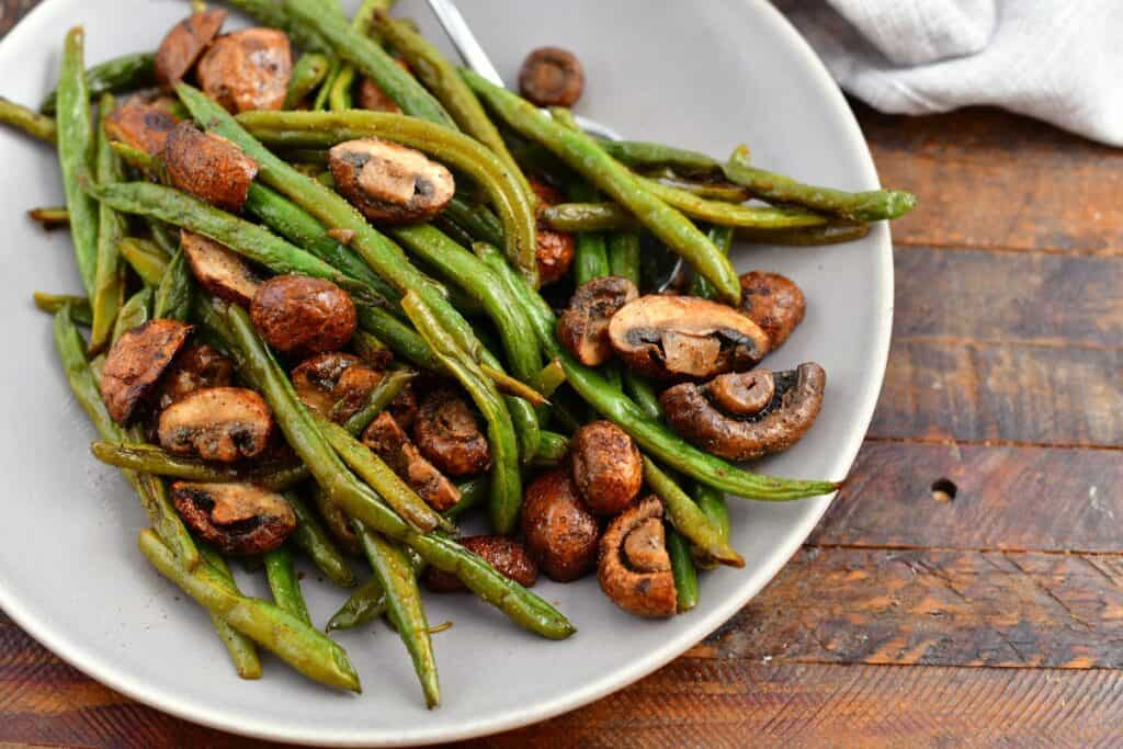 overhead: fresh vegetable side dish in white bowl (green beans and mushrooms)
