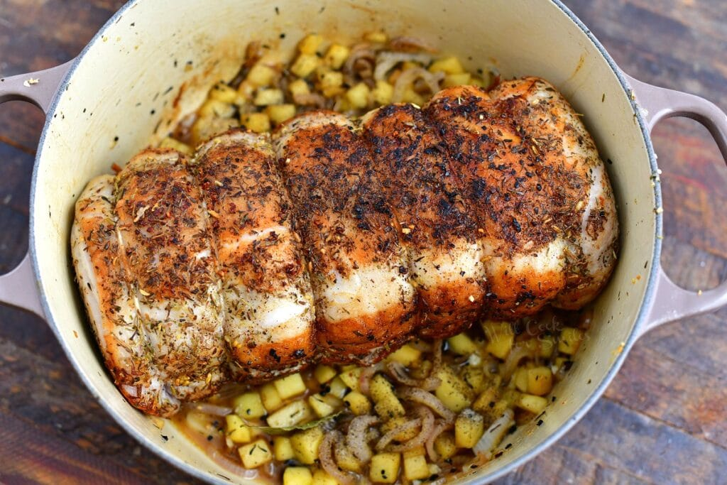 roasting pork loin in white pot with diced vegetables