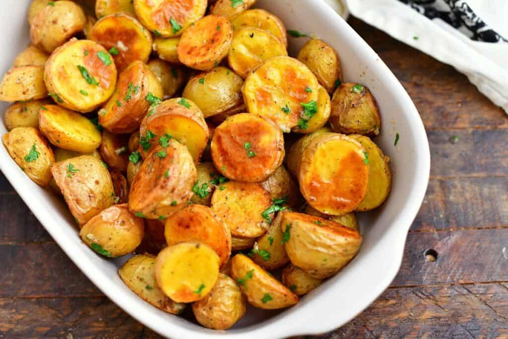 white dish of oven roasted potatoes with parsley and melted butter in white serving dish