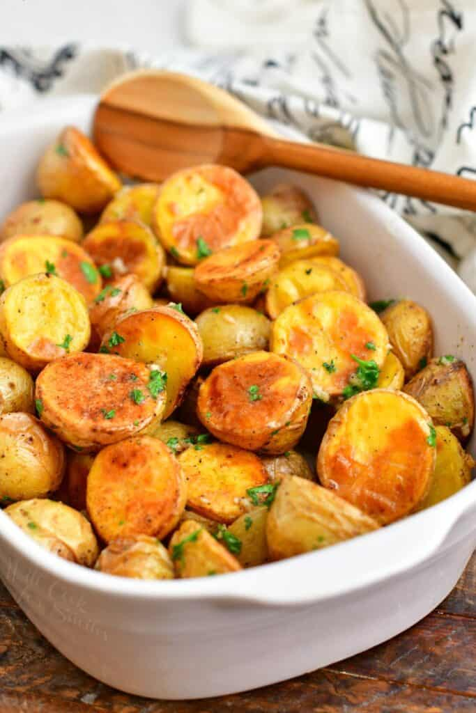 wooden spoon in white casserole dish with roasted potatoes