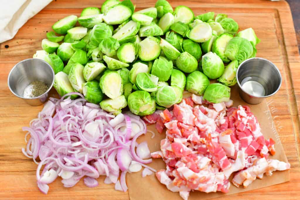 bacon, shallots and brussels sprouts on wooden cutting board