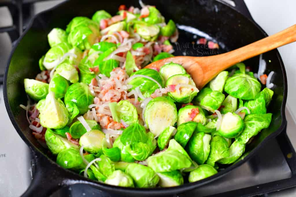 cooking green vegetables, shallot, and bacon in black skillet