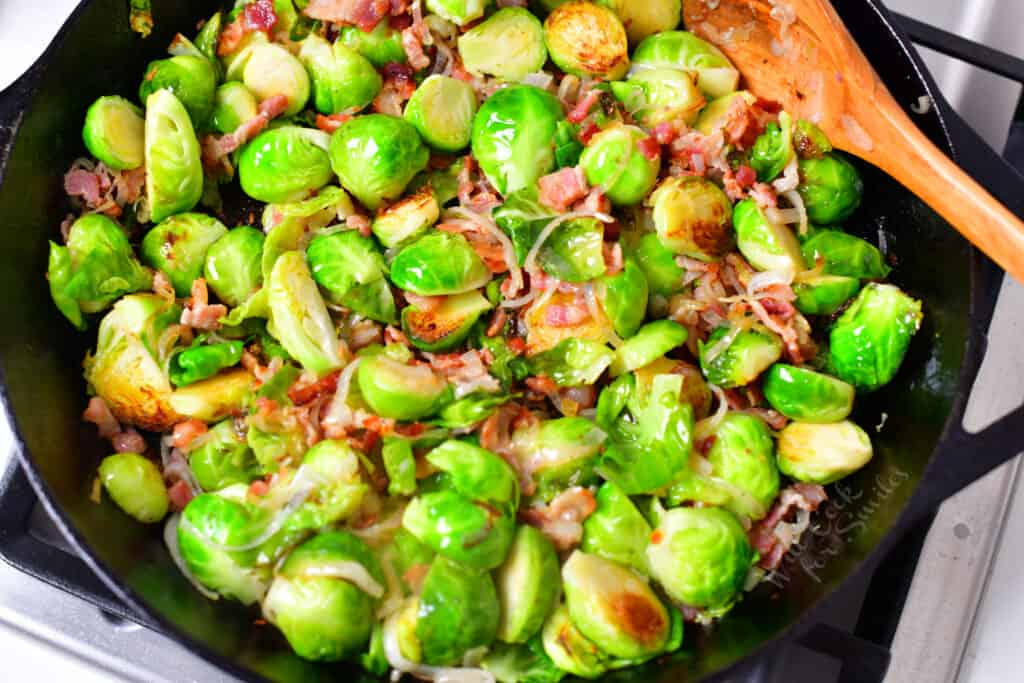 pan fried Brussels sprouts and bacon in skillet with wooden spoon
