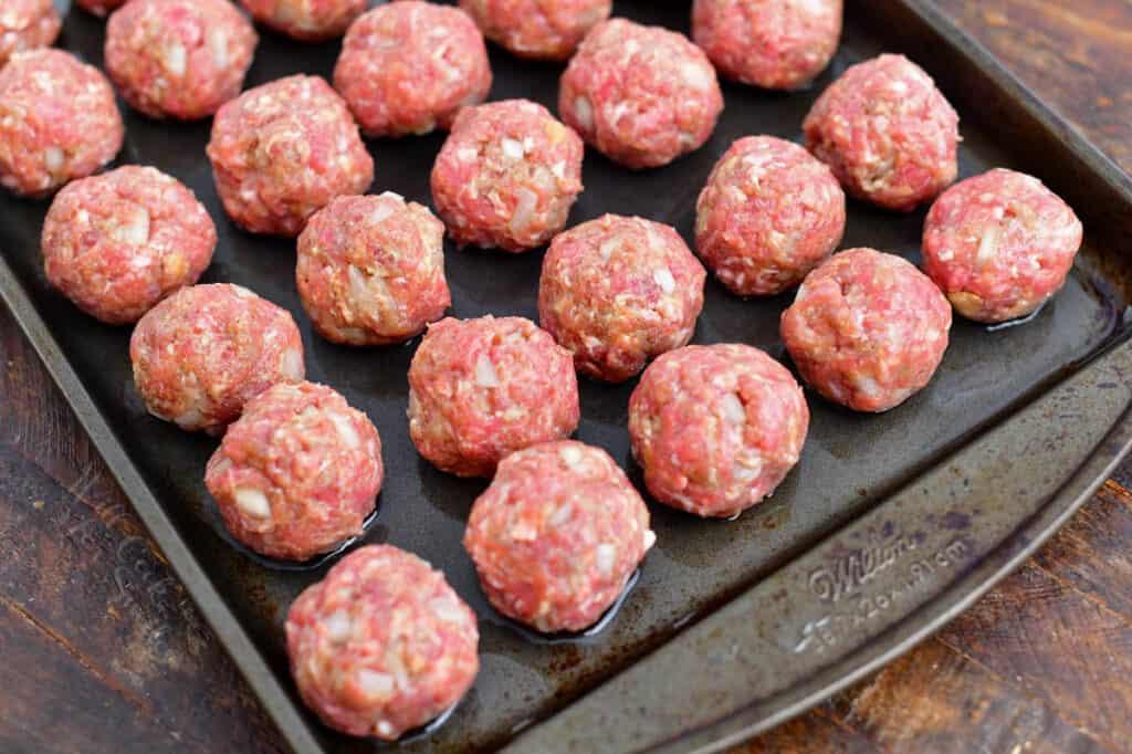 uncooked beef appetizer meatballs on baking sheet