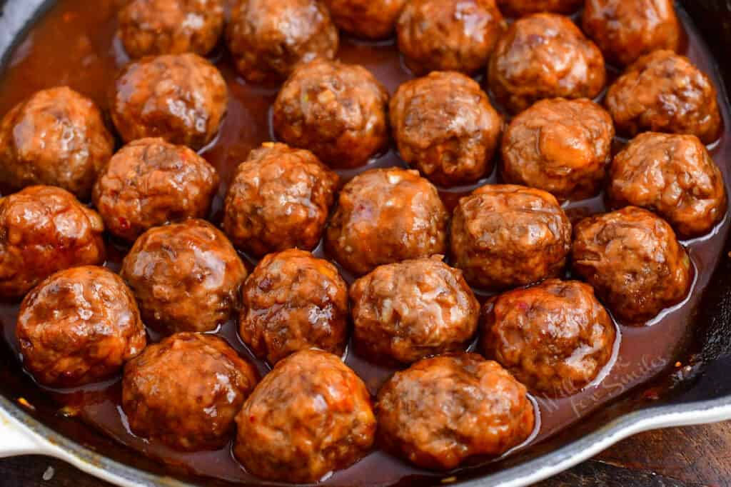 bite-sized meatballs simmering in cocktail meatball sauce