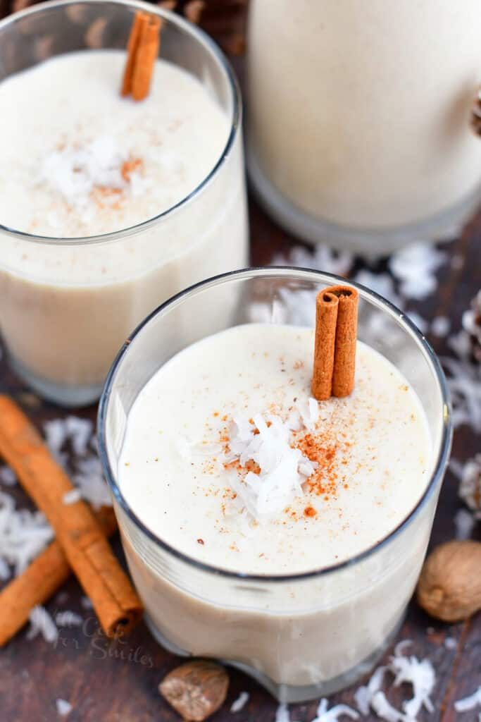 Puerto Rican Christmas drink in 2 glasses with cinnamon sticks and coconut garnish