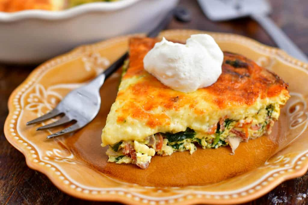 A slice of crustless quiche on a brown plate with a dollop of sour cream on top.