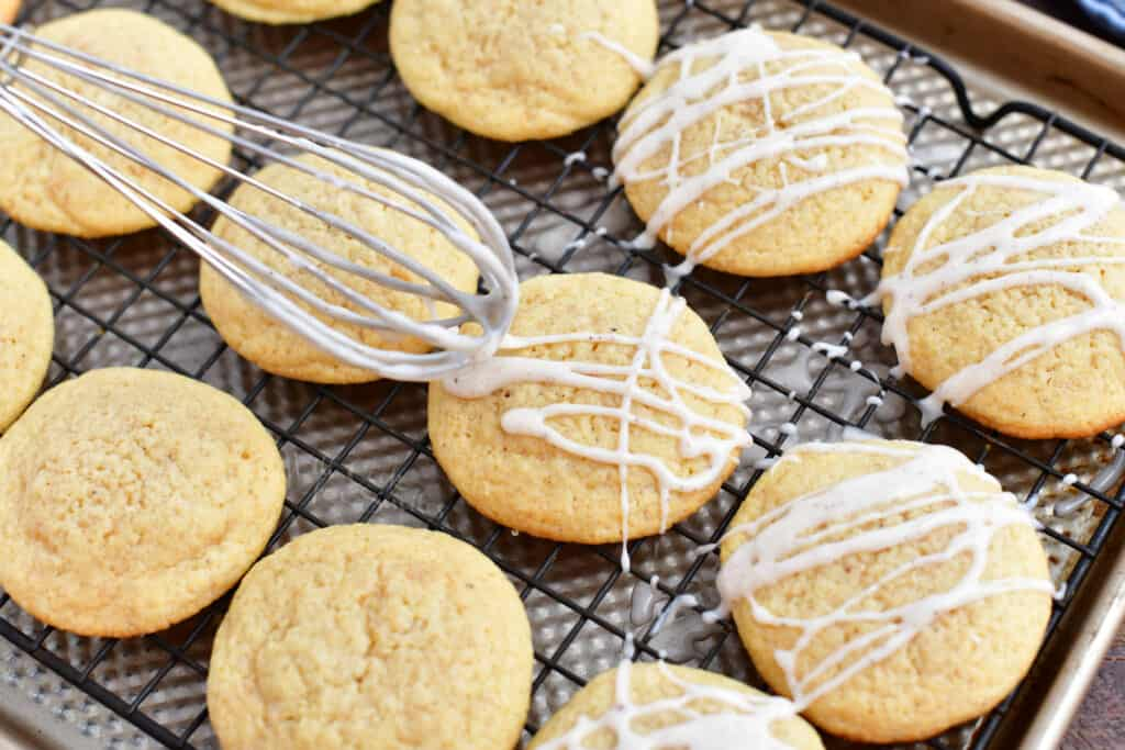 Icing is drizzled from a whisk onto the freshly baked cookies.