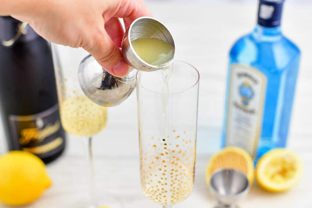 Lemon juice is poured into a sparkly glass for a French 75 recipe