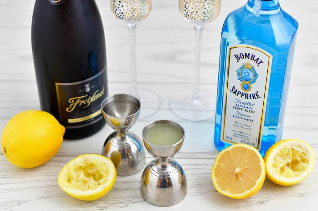 The ingredients and tools needed to make a French 75 recipe, on a white surface.