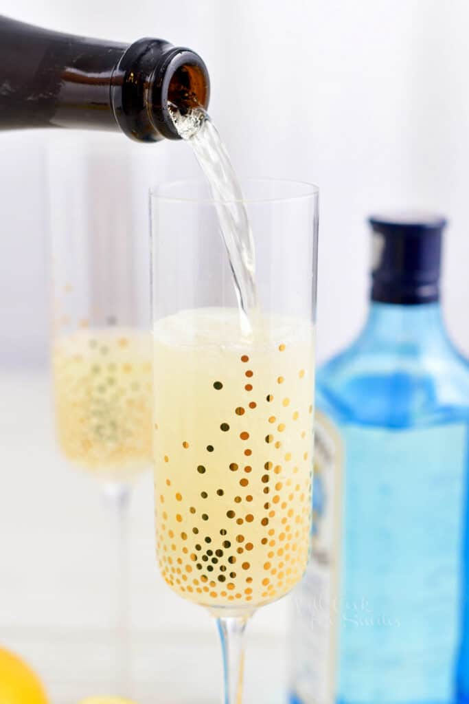 pouring champagne into a tall stemmed glass