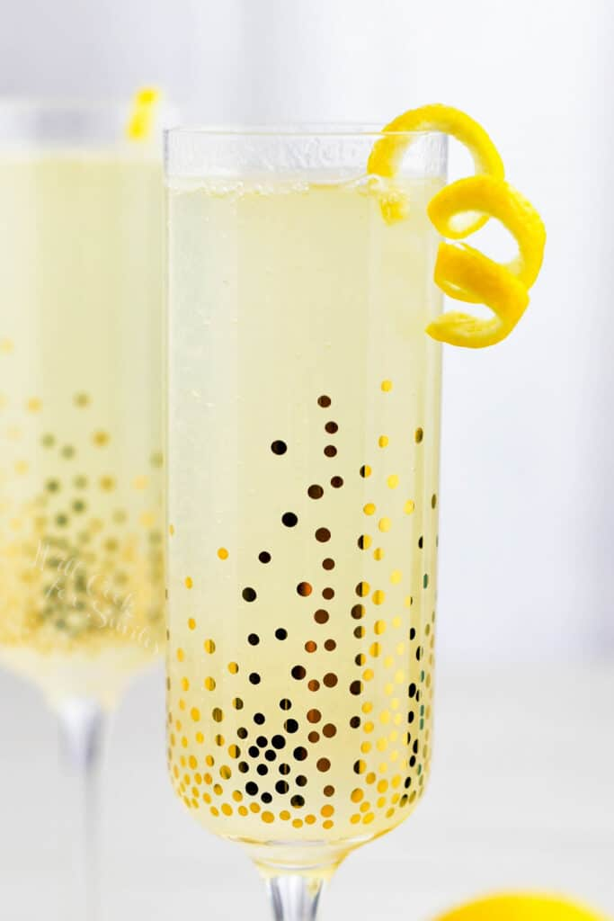 A French 75 is served in a sparkling, golden glass with a sliver of orange peel.