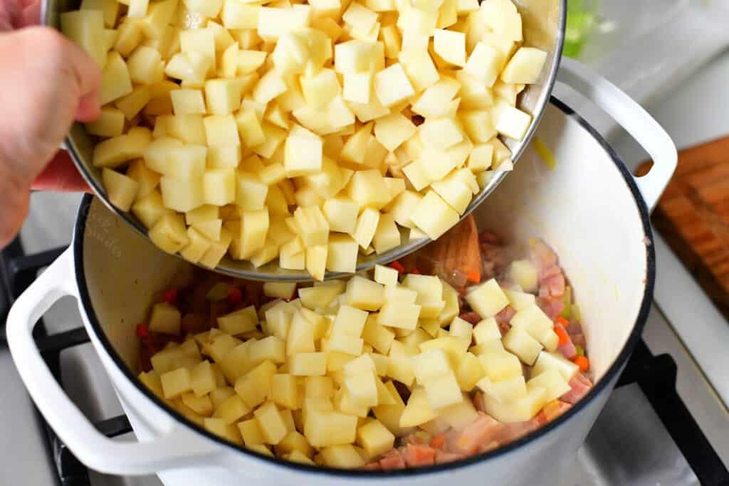 adding diced potatoes into a pot of ham soup