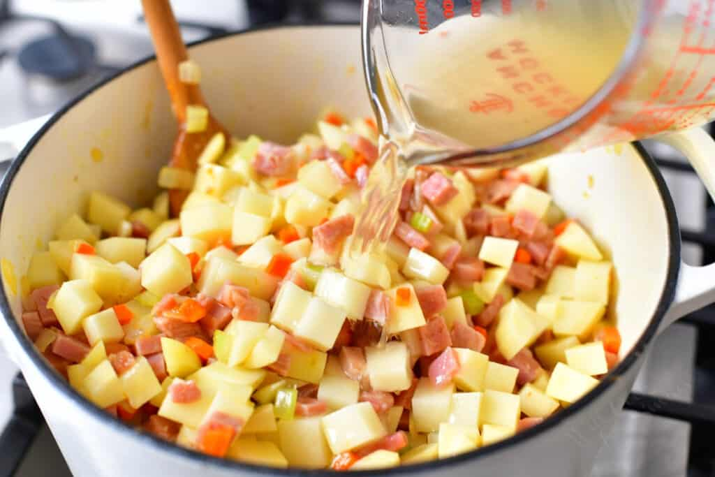 adding chicken stock to a pot of vegetables, potatoes and ham for soup recipe
