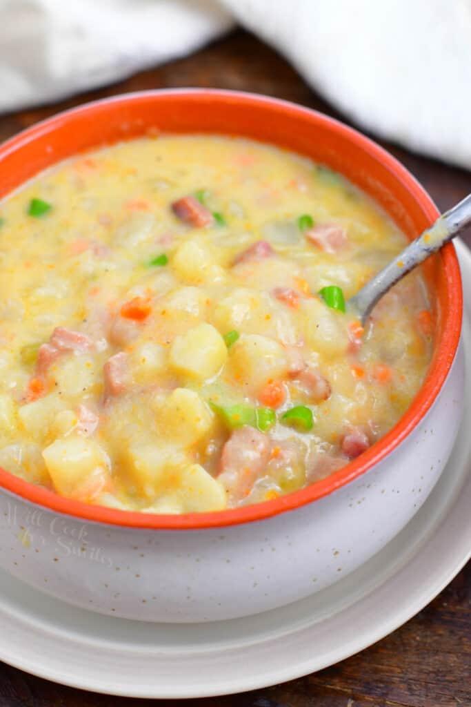 overhead image: spoon in orange bowl of creamy ham chowder