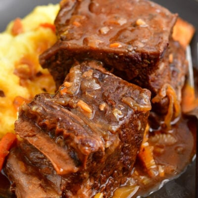 A serving of short ribs is served on top of mashed potatoes.