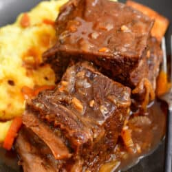 Two pieces of short rib sit on top of a helping of mashed potatoes.