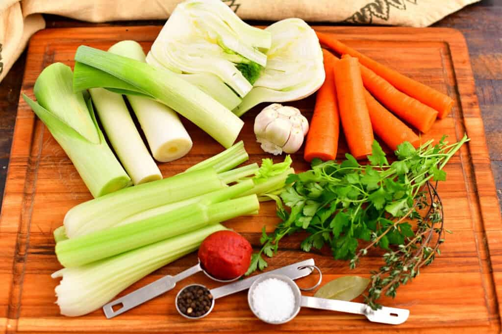 fresh vegetables, herbs, and spices on cutting board to make vegetable stock