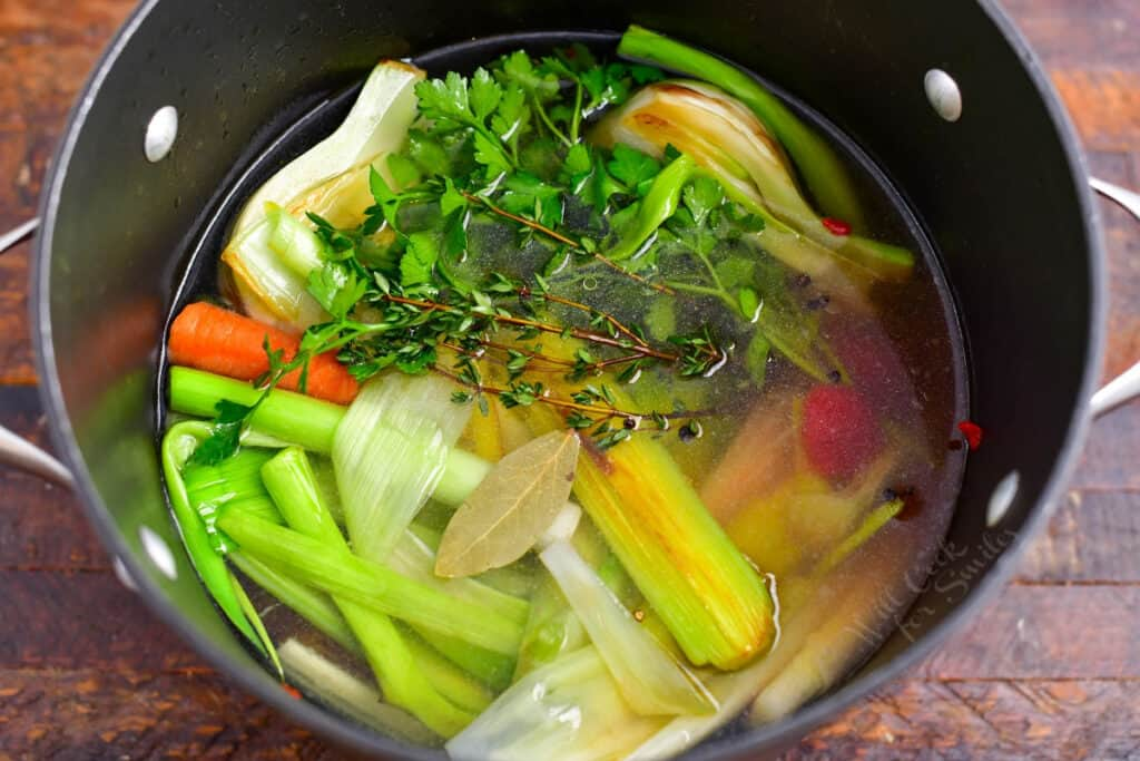 overhead photo: fresh vegetables and herbs cooking in large stock pot to make vegetable broth