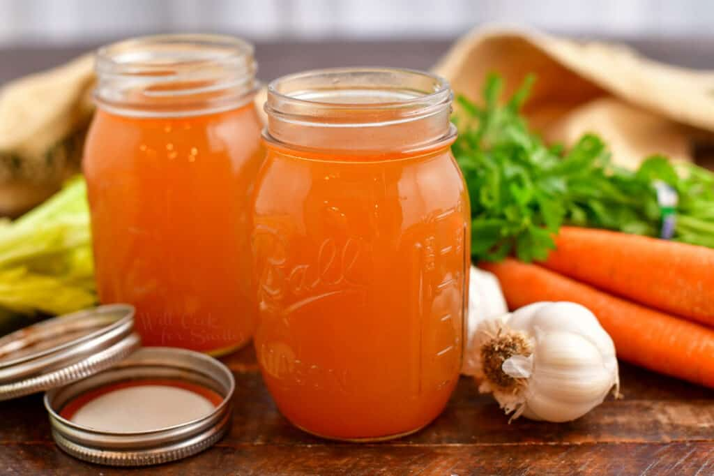 vegetable broth in two canning jars next to fresh carrots, garlic, and celery