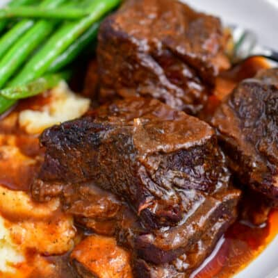 braised beef ribs on plate with green beans and mashed potatoes