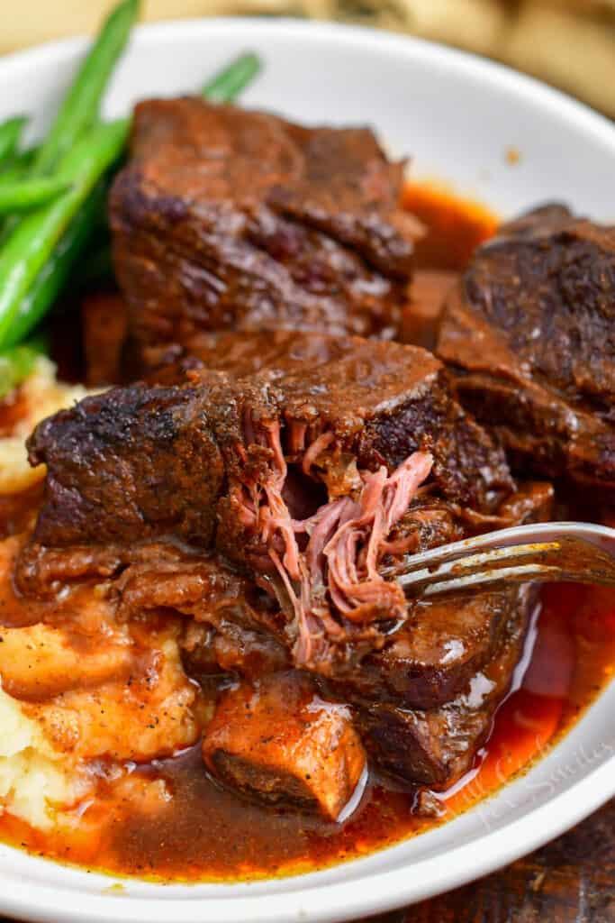 fork pulling tender meat from braised short ribs
