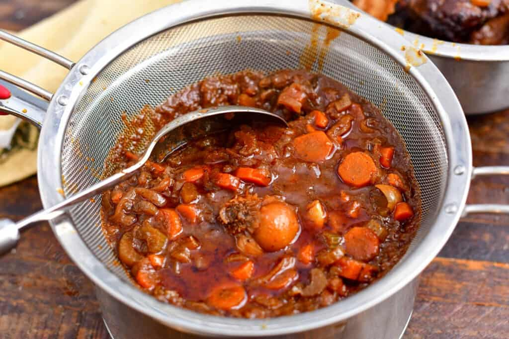 vegetables and braising ingredients in fine mesh strainer