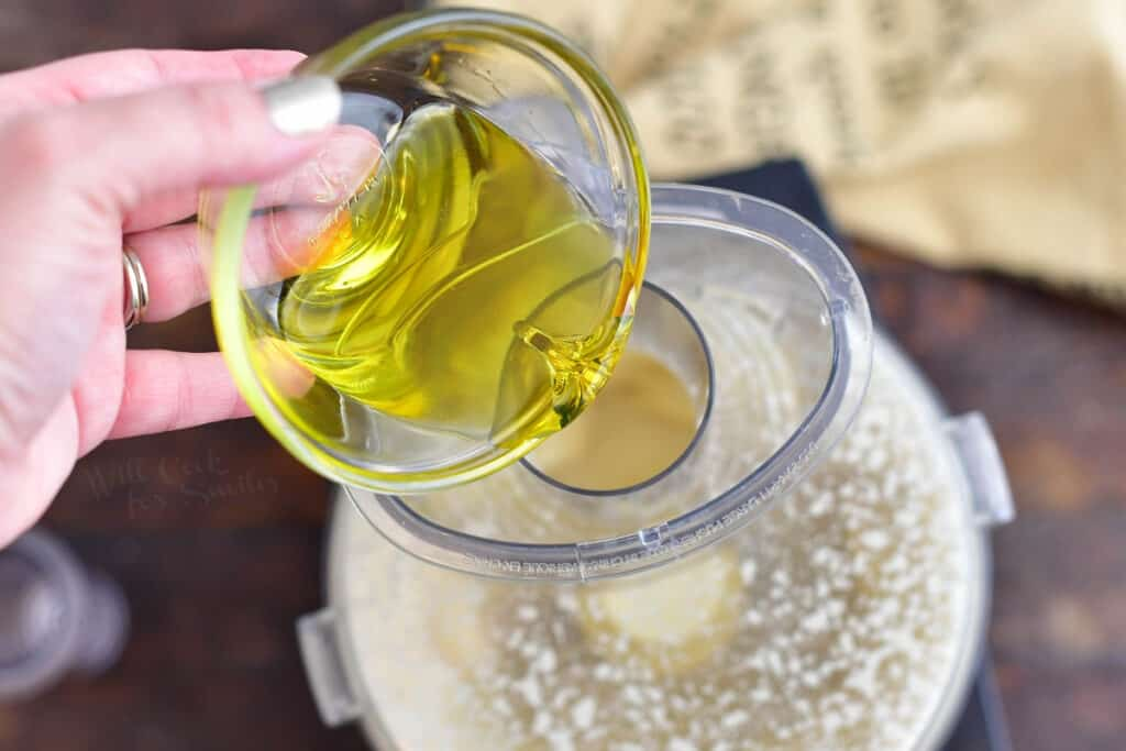 pouring olive oil into food processor for homemade salad dressing