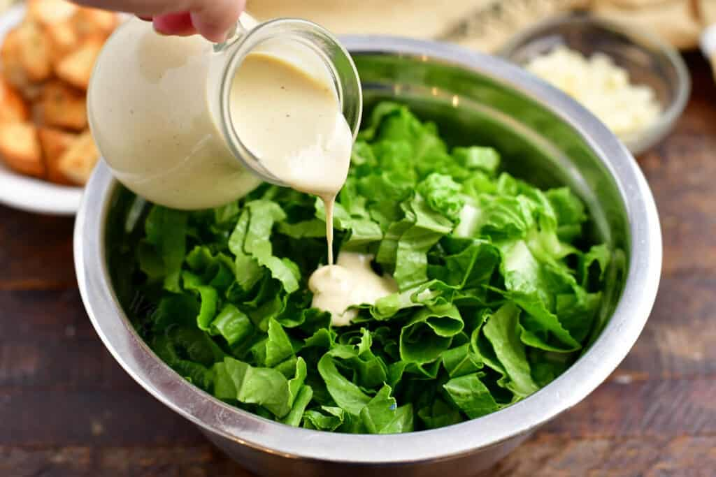 pouring white salad dressing over romaine lettuce leaves in salad bowl