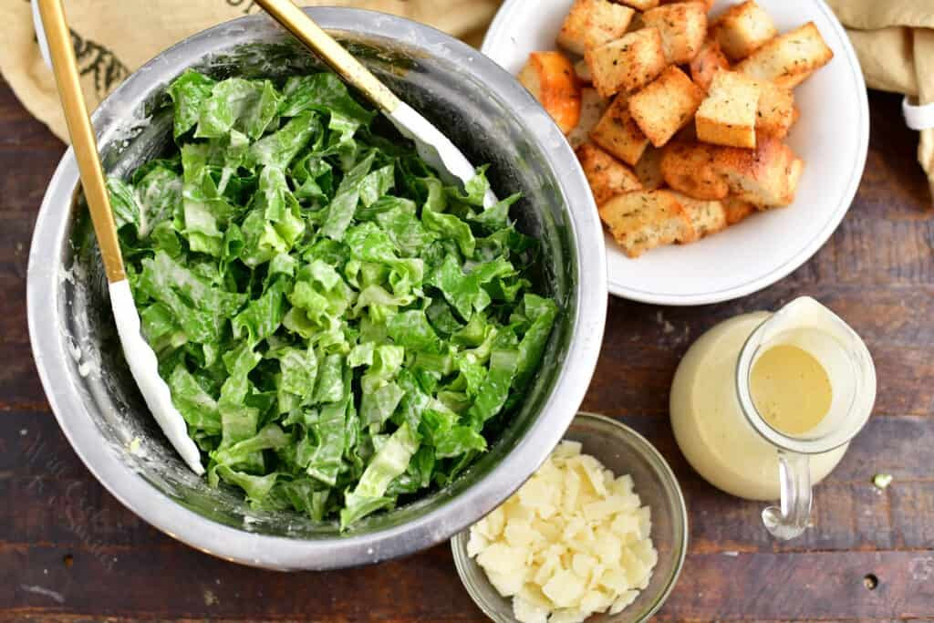 tossing a classic caesar salad with dressing in a bowl