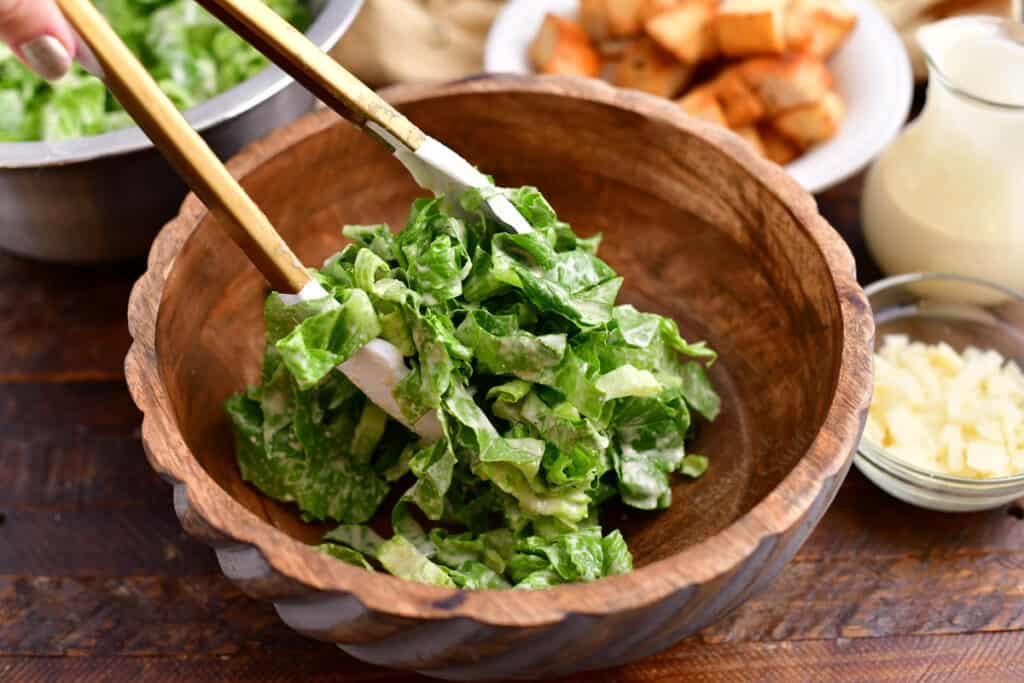 using tongs to serve salad into small bowl