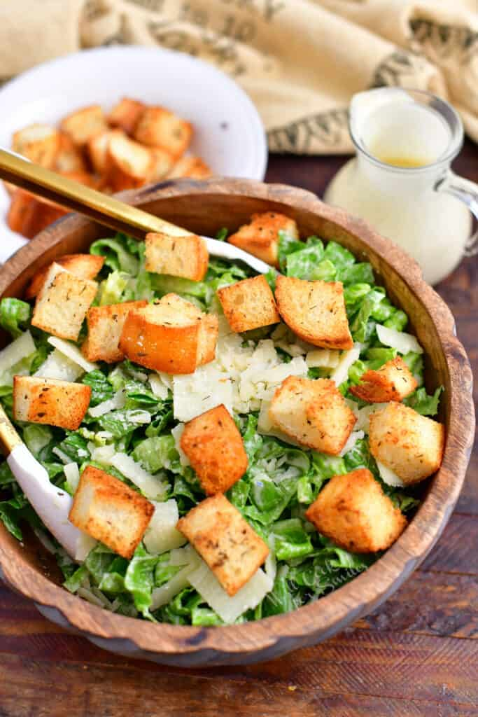 homemade caesar salad with garlic croutons and dressing in wooden bowl